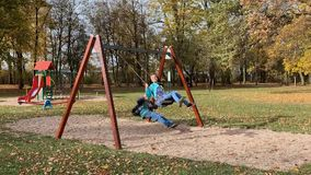 Dzieci na huśtawkach przy boiskiem zdjęcie wideo