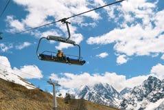 Dzieci na otwartym wagonie kolei linowej jadą w śnieżnych górach zdjęcia royalty free