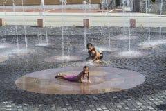 Dzieci na pogodny ciepły dnia bawić się outside w wodnej fontannie Dzieci szczęśliwie w płytkiej czystej wodzie dalej miasto font fotografia royalty free