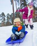 Dzieci na saniach w śniegu Zdjęcia Stock