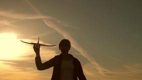 Dzieci na tle s?o?ce z samolotem w r?ce Dziewczyny sztuka z zabawkarskim samolotem przy zmierzchem Sen latanie Szcz??liwy zbiory