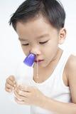 Dzieci nosowi czyścą zasolonym rozwiązaniem Obrazy Royalty Free