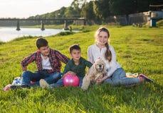 Dzieci odpoczywa na trawie w parku Fotografia Stock