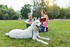 Dzieci odpoczywają w parku z psem zdjęcie stock