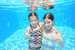 Dzieci pływają w basenie podwodnym, szczęśliwe aktywne dziewczyny zabawę pod wodą Obraz Royalty Free