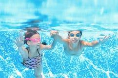 Dzieci pływają w basenie podwodnym, szczęśliwe aktywne dziewczyny zabawę pod wodą, dzieciak sprawnością fizyczną i sportem na rod zdjęcie royalty free