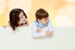 Dzieci patrzeją out od sztandaru za Fotografia Stock