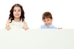 Dzieci patrzeją out od sztandaru za Obraz Royalty Free