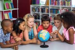 Dzieci patrzeje kulę ziemską na stole Zdjęcie Stock