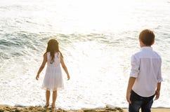 Dzieci patrzeje morze z jego plecy kamera zdjęcie royalty free
