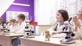 Dzieci patrzeje w mikroskop, studing biologia, chemia w szkolnym laboratorium zdjęcie wideo