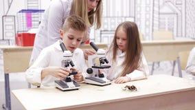 Dzieci patrzeje w mikroskop, studing biologia, chemia w szkolnym laboratorium Szkolny nauki pojęcie zdjęcie wideo