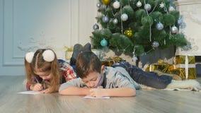 Dzieci piszą listach Święty Mikołaj Dzieci ja jest rozochocony Chłopiec i dziewczyna kłamamy na podłogowych pobliskich boże narod zbiory