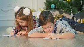 Dzieci piszą listach Święty Mikołaj Dzieci ja jest rozochocony Chłopiec i dziewczyna kłamamy na podłogowych pobliskich boże narod zbiory wideo