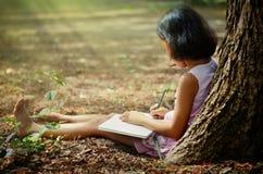 Dzieci pisze książce pod drzewem Zdjęcie Stock