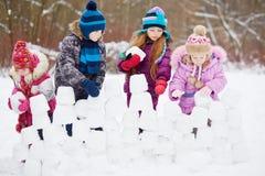 Dzieci pracują przy budynek ścianą od śnieżnych bloków zdjęcia royalty free