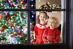 Dzieci przy choinką Dzieciaki przy grabą na Xmas wigilii Zdjęcie Stock