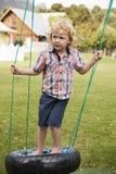 Dzieci Przy Montessori szkołą Bawić się Na huśtawkach Podczas przerwy zdjęcia stock