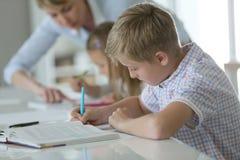Dzieci przy szkolnym pisze puszkiem Zdjęcia Royalty Free
