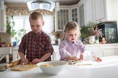 Dzieci przygotowywa ciastka w kuchni Obrazy Royalty Free