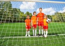 Dzieci różny wzrosta stojak z futbolem Obraz Stock