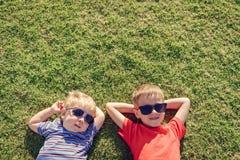 Dzieci relaksuje na zielonej trawie obrazy royalty free