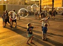 Dzieci robi wielkim mydlanym bąblom Fotografia Royalty Free