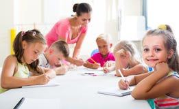 Dzieci robi writing ćwiczą z pomocą nauczyciel w klasie Fotografia Stock