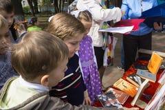 Dzieci rozważają książki i dzieci rysunki o wojnie w parku Fotografia Royalty Free
