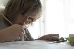Dzieci rysują w domu, chłopiec studiowania rysunek przy szkołą Obrazy Royalty Free