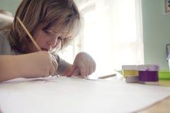 Dzieci rysują w domu, chłopiec studiowania rysunek przy szkołą Fotografia Royalty Free