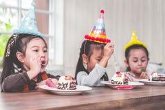 Dzieci są szczęśliwym łasowaniem jej urodzinowy tort w przyjęciu zdjęcia royalty free