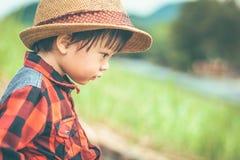 Dzieci są ubranym kapelusz i obsiadanie na ziemi w gospodarstwie rolnym fotografia royalty free