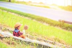 Dzieci są ubranym kapelusz i obsiadanie na schodku Dziecko chwyta kwiat blisko drogi i obraz stock