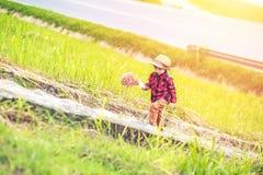 Dzieci są ubranym kapelusz i odprowadzenie na schodku Dziecko chwyta kwiat blisko drogi i zdjęcie stock