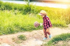Dzieci są ubranym kapelusz i odprowadzenie na schodku Dziecko chwyta kwiat blisko drogi i obraz stock