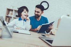 dzieci się uśmiecha ojciec homework Laptop wychowanie zdjęcie stock