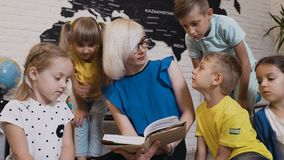 Dzieci siedzą na podłoga na poduszkach gdy nauczyciel czyta one ciekawą książkę w klasie przy szkołą podstawową lub zbiory wideo