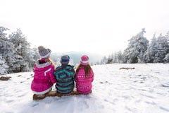 Dzieci siedzi na narciarskim terenie, tylny widok Zdjęcie Royalty Free