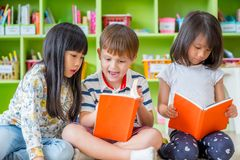 Dzieci siedzi na podłoga i czytelniczej bajce rezerwują w preschool li zdjęcia royalty free