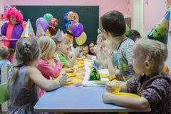 Dzieci siedzi ?wi?tecznym sto?em Wszystkiego najlepszego z okazji urodzin ch?opiec w ogr?dzie troszk? zdjęcie stock