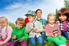 Dzieci siedzi z magnifier i pisze notatkach Fotografia Stock