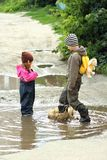 Dzieci skacze i bryzga w błotnistych kałużach Obraz Stock