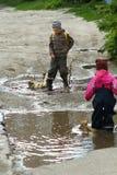Dzieci skacze i bryzga w błotnistych kałużach Obrazy Royalty Free