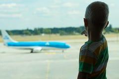 Dzieci spojrzenia przy samolotem przez okno lotnisko fotografia royalty free