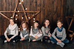 Dzieci stoją przeciw tłu nowego roku ` s gwiazda obrazy stock