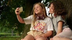 Dzieci?stwo czas Śliczne Uśmiechnięte małe dziewczynki Cieszy się w parku Podczas gdy Robić słuchaniu I Selfie muzyka Z wiszącą o zdjęcie wideo