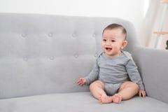 Dzieci?stwo, niemowl?ctwo i ludzie poj??, - szcz??liwy ma?y dziewczynki obsiadanie na kanapie w domu zdjęcie stock