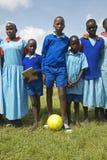 Dzieci trzyma piłki nożnej piłkę przy szkołą blisko Tsavo parka narodowego w błękitnych mundurach, Kenja, Afryka Obrazy Royalty Free