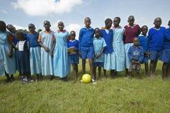 Dzieci trzyma piłki nożnej piłkę przy szkołą blisko Tsavo parka narodowego w błękitnych mundurach, Kenja, Afryka Zdjęcia Royalty Free